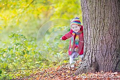 Baby girl in red coat hiding behind big old