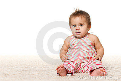 Baby girl is sitting on the carpet