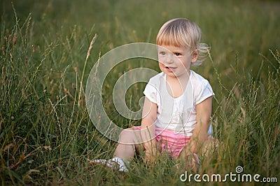 Baby girl sitting in grass