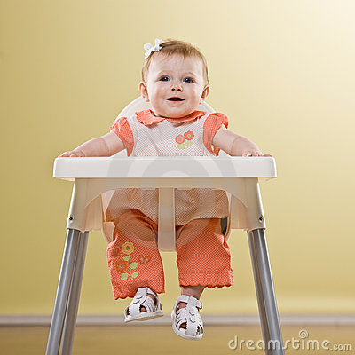 Baby girl sitting in highchair waiting to be fed