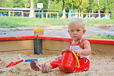Baby girl sitting playing in a sandbox