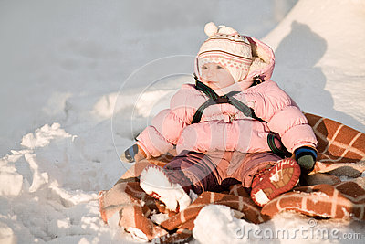 Baby girl sitting on snow