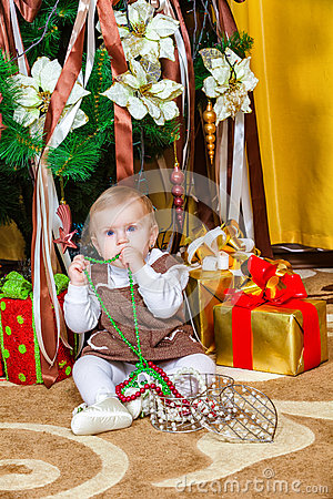 Baby girl sitting under christmas tree in room