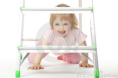 The baby girl is sitting under a stepladder