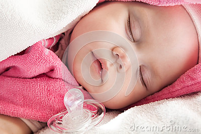 Baby girl sleeps with a pacifier nearby
