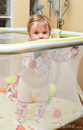 Baby girl stand in playpen