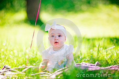 Baby girl on a sunny meadow portrait Stock Photo