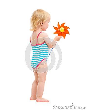 Baby girl in swimsuit holding pinwheel