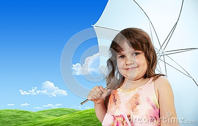 Baby girl with umbrella on green meadow