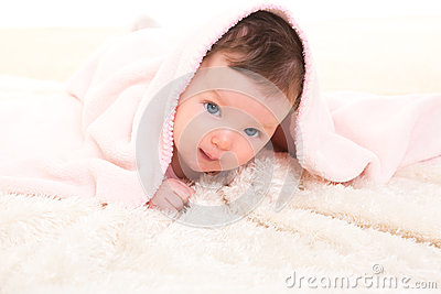 Baby girl under hidden pink blanket on white fur