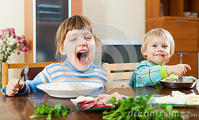 Baby girls eating food at table Stock Photo