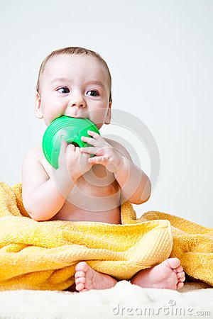 Baby Gnawing Green Toy on Yellow Towel