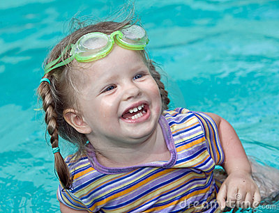 Baby in  goggles swim pool.