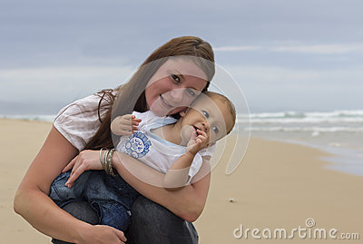 Baby boy with happy mother on beach, smile