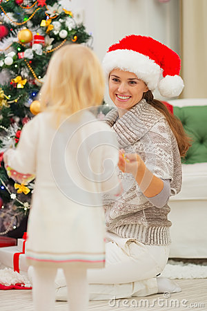 Baby helping mother decorate Christmas tree