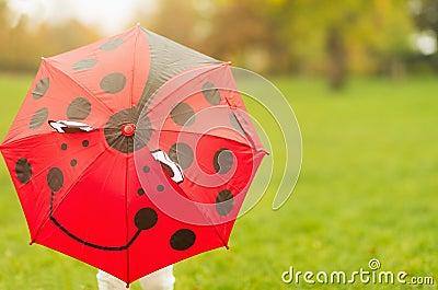 Baby hiding behind red umbrella