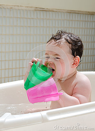 Baby holding 2 cups in a bathtub