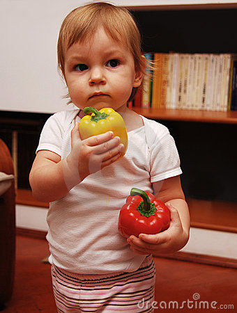 Baby holding peppers