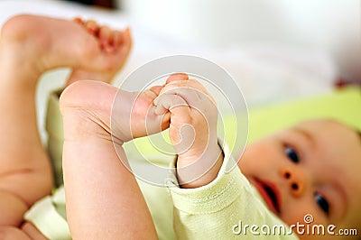Baby holds feet