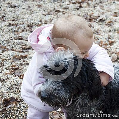 Baby hugging dog.