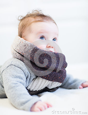 Free Baby In A Frey Knitted Sweater And Big Brown Scarf Royalty Free Stock Images - 41162709