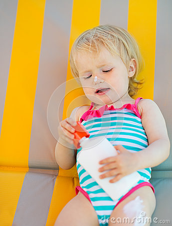 Baby laying on sun bed with sun block bottle