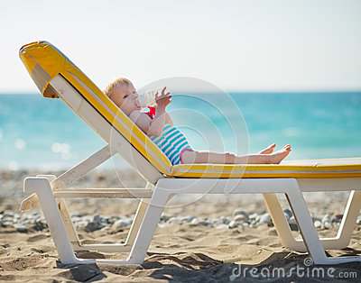 Baby laying on sunbed and drinking water