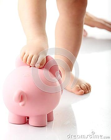 Baby legs on piggy bank