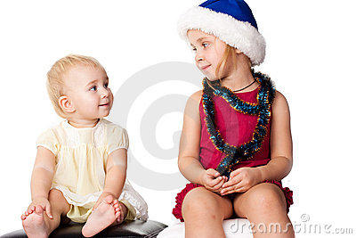 Baby looking at the sibling sister in Santa s hat
