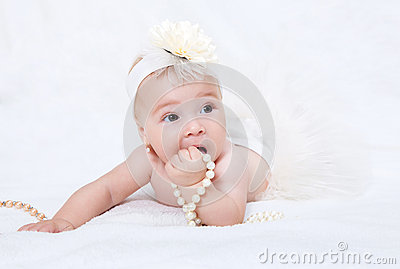 Baby lying in bed with a pearl necklace