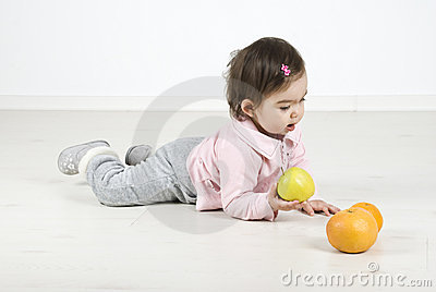Baby lying on floor with fruits