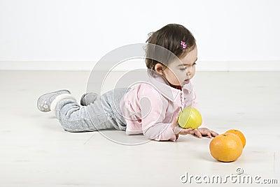Baby lying on floor with fruits
