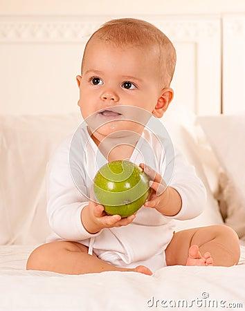 Baby manipulating green apple