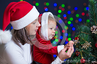 Baby with mother decorate Christmas tree on bright