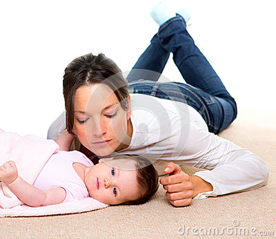 Baby and mother lying on beige carpet together