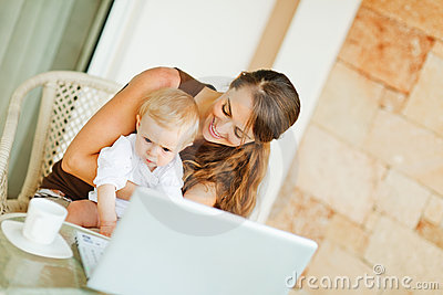Baby with mother working on laptop