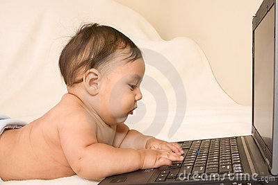 Baby with notebook portable computer, typing