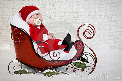 Baby with pacifier in Christmas sleigh