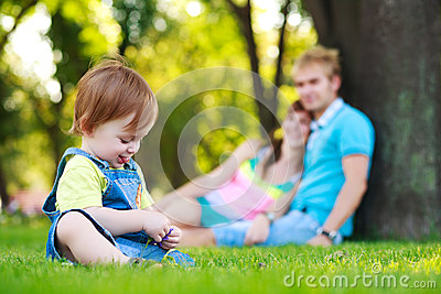 Baby playing with parents in a beautiful park
