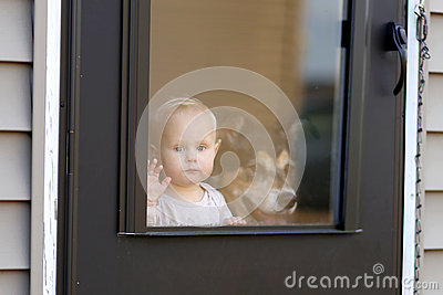 Baby And Pet Dog Waiting At Door Looking Out Window Stock