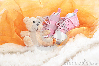Baby pink shoes and teddy bear