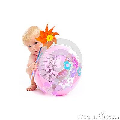 Baby with pinwheel hiding behind beach ball