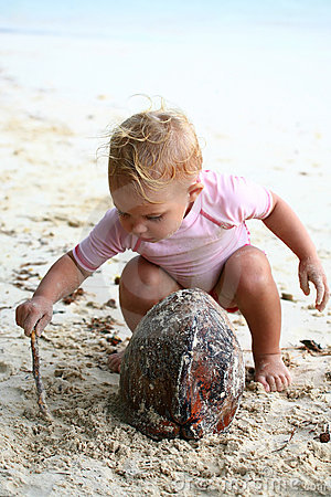 Baby playing with coconut