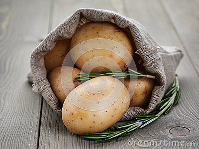 Baby potatoes in sack bag with rosemary Stock Photo