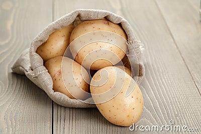 Baby potatoes in sack bag Stock Photo