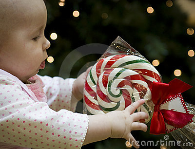 Baby reaching for Christmas Candy Cane Lollipop