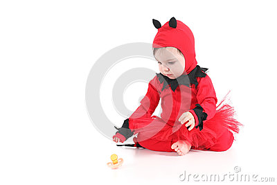 Baby with a red demon disguise watching a pacifier