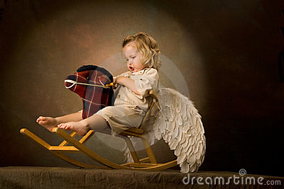 Baby rides a woody horse