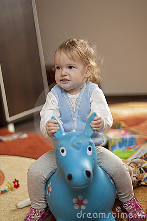 Baby riding a toy horse