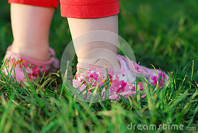 Baby`s feet on green grass
